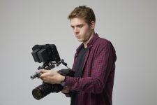 studio-portrait-of-male-videographer-with-film-camera.jpg